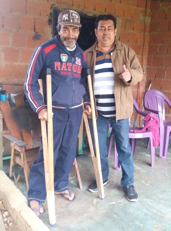 João Rodrigues em Sanga Puitã recebendo um par de muletas de Zadir de Souza, Presidente do Clube de Imprensa de Ponta Porã